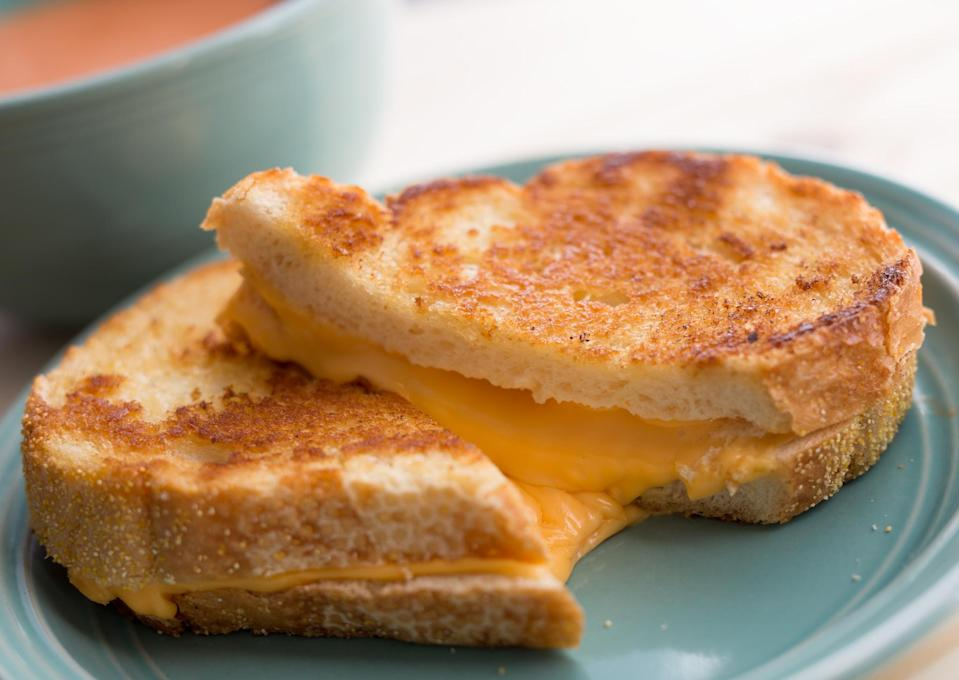 "<p>There are three things you can do to take your basic grilled cheese to the next level. First, skip the Wonder Bread and use something a little heftier and a little nicer, like sliced sourdough. Second, slather a mix of butter and mayo on that bread — at the end of the day, <a href=""https://www.thedailymeal.com/recipes/homemade-mayonnaise-recipe-1?referrer=yahoo&category=beauty_food&include_utm=1&utm_medium=referral&utm_source=yahoo&utm_campaign=feed"" rel=""nofollow noopener"" target=""_blank"" data-ylk=""slk:mayo is just egg, olive oil, lemon juice and salt"" class=""link rapid-noclick-resp"">mayo is just egg, olive oil, lemon juice and salt</a>. These simple ingredients help to get the sandwich that perfect shade of golden brown while adding a slightly nutty flavor. Finally, use two shredded cheeses: American <em>and</em> cheddar. The cheddar adds some crowd-pleasing flavor to simple American cheese, and using shredded cheeses instead of slices leads to an even melt and cheese distribution. Cook your super sandwich on each side for 3 to 4 minutes over medium heat, and you'll never go back to the old days.</p> <p><a href=""https://www.thedailymeal.com/ultimate-grilled-cheese-recipe?referrer=yahoo&category=beauty_food&include_utm=1&utm_medium=referral&utm_source=yahoo&utm_campaign=feed"" rel=""nofollow noopener"" target=""_blank"" data-ylk=""slk:For the Best Grilled Cheese recipe, click here."" class=""link rapid-noclick-resp"">For the Best Grilled Cheese recipe, click here.</a></p> <p>While this recipe is pretty darn great, there are still ways to make your grilled cheese EVEN better...</p>"