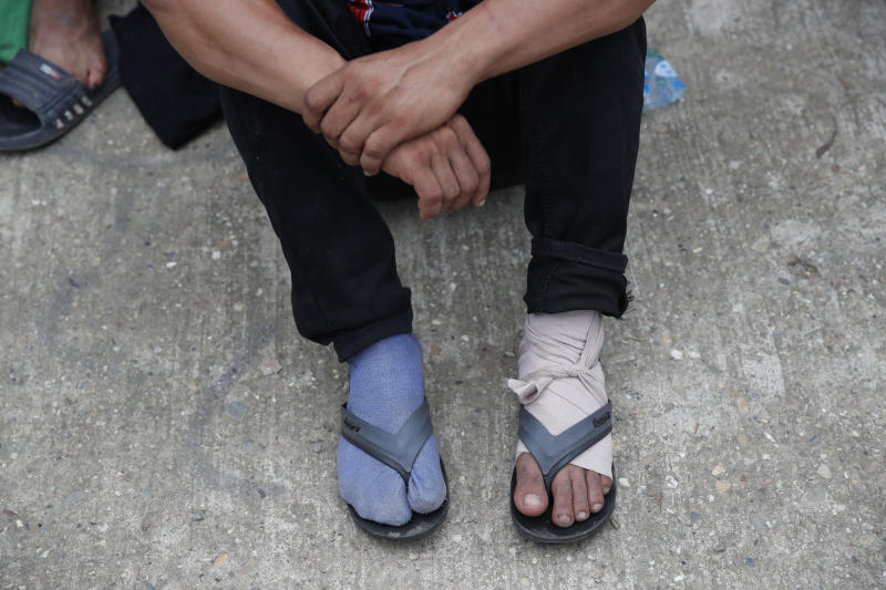 "A Honduran migrant with a bandaged foot awaits medical attention from Guatemalan Red Cross paramedics before he is deported after the group he was traveling with was stopped by police in Morales, Guatemala, Thursday, Jan. 16, 2020. Less-organized migrants, tighter immigration control by Guatemalan authorities and the presence of U.S. advisers have reduced the likelihood that the hundreds of migrants who departed Honduras will form anything like the cohesive procession the term ""caravan"" now conjures. (AP Photo/Moises Castillo)"