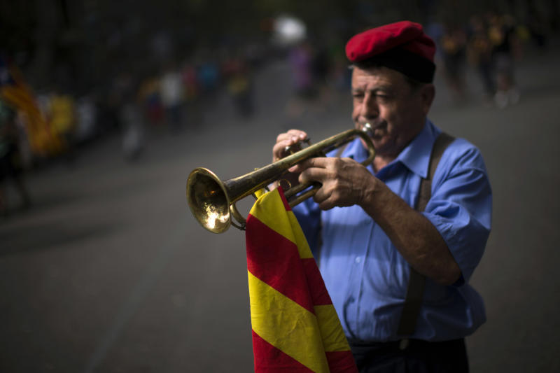 "Ferran Estrada Porta, 79, wearing the traditional cup or ""barretina"" and holding a Catalan flag, plays his trumpet on the street in Barcelona, Spain, Tuesday, Sept. 11, 2012. Thousands of people demonstrated in Barcelona on Tuesday to join a rally demanding independence for Catalonia, in northeastern Spain, on the Catalan national day. (AP Photo/Emilio Morenatti)"