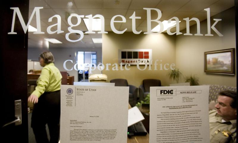 In this Monday, Feb. 2, 2009, file photo, FDIC, bank personnel and a sheriff deputy work inside the corporate office of MagnetBank in Salt Lake City. The banking industry has come a long way since the financial crisis struck in 2008. A sturdier economy, healthier loan portfolios, low interest rates, higher fees on bank accounts and a wave of mergers have combined to reduce the number of bank failures. (AP Photo/Douglas C. Pizac, File)