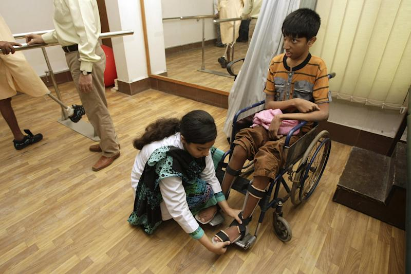 In this picture taken on Saturday, March 30, 2013, a Pakistani female doctor helps a disabled child at a rehabilitation center at the Dow Medical Institute for Health in Karachi, Pakistan. In a country better known for honor killings of women and low literacy rates for girls, Pakistan's medical schools are a reflection of how women's roles are evolving. Women now make up the vast majority of students studying medicine, a gradual change that's come about after a quota favoring male admittance into medical school was lifted in 1991. (AP Photo/Fareed Khan)