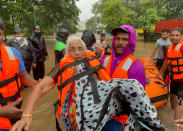 A National Disaster Response Force personnel rescues an elderly woman stranded in floodwaters in Kolhapur, in the western Indian state of Maharashtra, Friday, July 23, 2021. Landslides triggered by heavy monsoon rains hit parts of western India, killing at least 32 people and leading to the overnight rescue of more than 1,000 other people trapped by floodwaters, officials said Friday. (AP Photo)