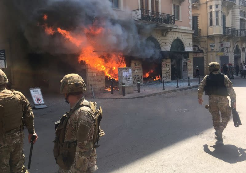 Lebanese soldiers are seen near a bank on fire during unrest, as an economic crisis brings demonstrations back onto the streets in Tripoli