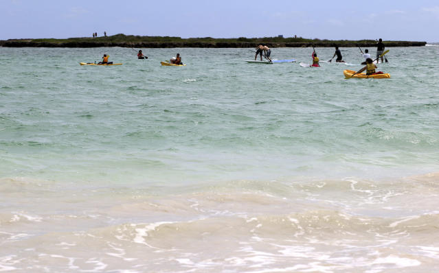 """In this May 15, 2019, photo, people paddle away from Kailua Beach Park in Kailua, Hawaii. In Kailua, the sand is soft and white, the water is clear and calm, and the view is exactly what you might expect from a beach in the Hawaiian Islands. Those are among the reasons the beach has been selected as the best stretch of sand on an annual list of top U.S. beaches. Stephen Leatherman, a coastal scientist and professor at Florida International University, has been drafting the list under the alias """"Dr. Beach"""" since 1991. (AP Photo/Caleb Jones)"""