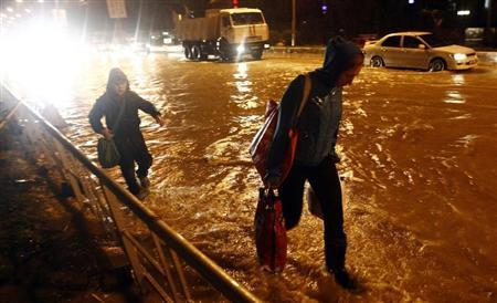 People walk along a flooded street in Sochi, September 24, 2013. REUTERS/Maxim Shemetov