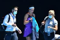 Victoria Azarenka leaves with the doctor (left) to receive medical attention during her defeat to Jessica Pegula