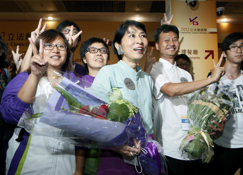 Claudia Mo Man-ching, center, of the pro-democracy Civic Party celebrates with her supporters after winning at a seat on the Legislative Council in Hong Kong, Monday, Sept. 10, 2012. Hong Kong voters cast ballots in legislative elections Sunday that will help determine the eventual shape of full democracy that Beijing has promised the former British colony. (AP Photo/Kin Cheung)
