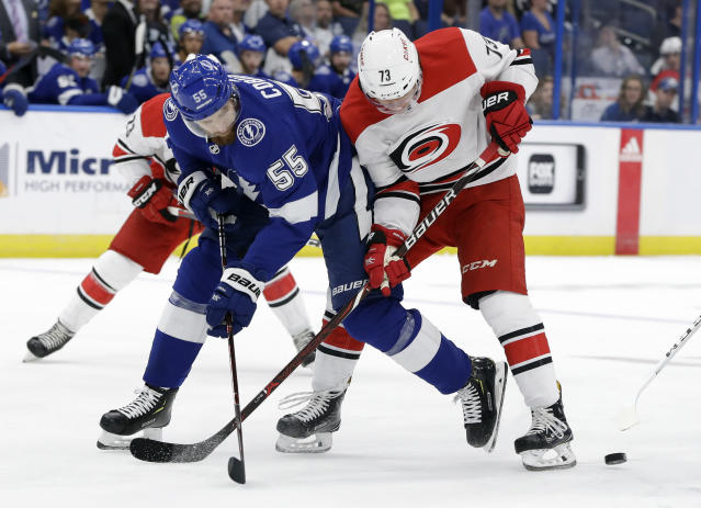 Tampa Bay Lightning defenseman Braydon Coburn (55) knocks the puck away from Carolina Hurricanes left wing Valentin Zykov (73) during the first period of an NHL hockey game Tuesday, Oct. 16, 2018, in Tampa, Fla. (AP Photo/Chris O'Meara)
