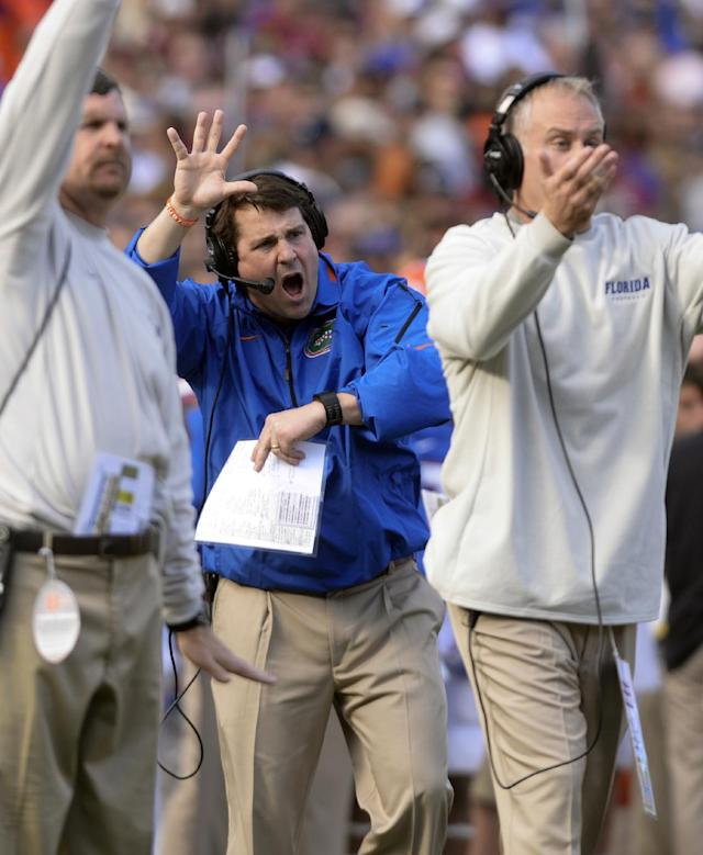 Florida coach Will Muschamp, center, and staff signals to his players during the second half of an NCAA college football game against Florida Saturday, Nov. 30, 2013 in Gainesville, Fla. Florida State won 37-7. (AP Photo/Phil Sandlin)