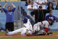 Los Angeles Dodgers' AJ Pollock, left, scores on a single by Zach McKinstry as Washington Nationals catcher Yan Gomes can't hold on to the throw during the second inning of a baseball game Saturday, April 10, 2021, in Los Angeles. (AP Photo/Mark J. Terrill)