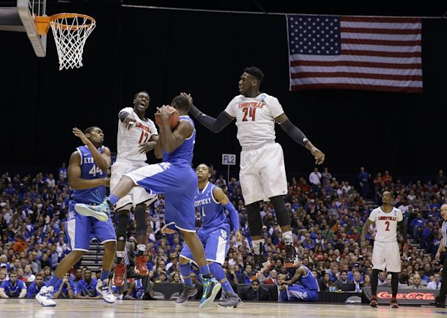 Kentucky's Julius Randle grabs a rebound in front of Louisville's Mangok Mathiang (12) and Montrezl Harrell (24) during the first half of an NCAA Midwest Regional semifinal college basketball tournament game Friday, March 28, 2014, in Indianapolis. (AP Photo/David J. Phillip)