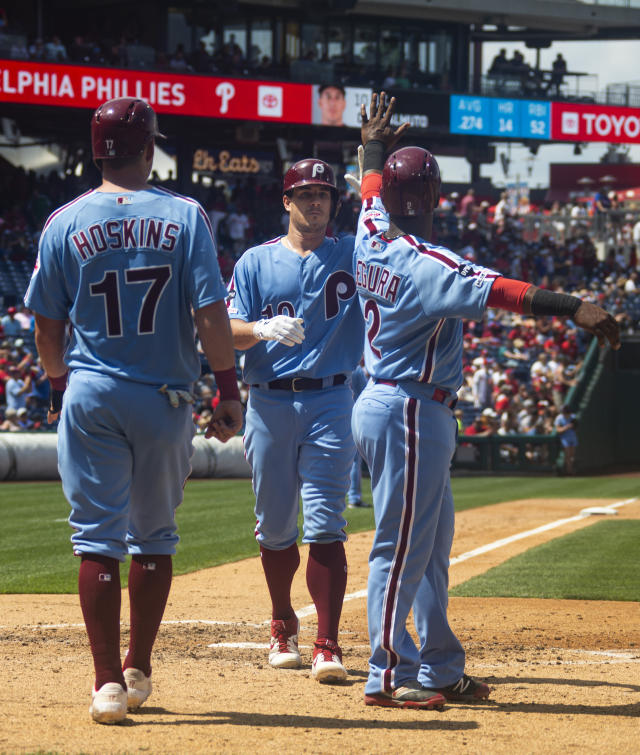 Philadelphia Phillies' J.T. Realmuto, center, celebrates his three-run home run with Jean Segura, right, and Rhys Hoskins, left during the fourth inning of a baseball game against the San Francisco Giants, Thursday, Aug. 1, 2019, in Philadelphia. (AP Photo/Chris Szagola)