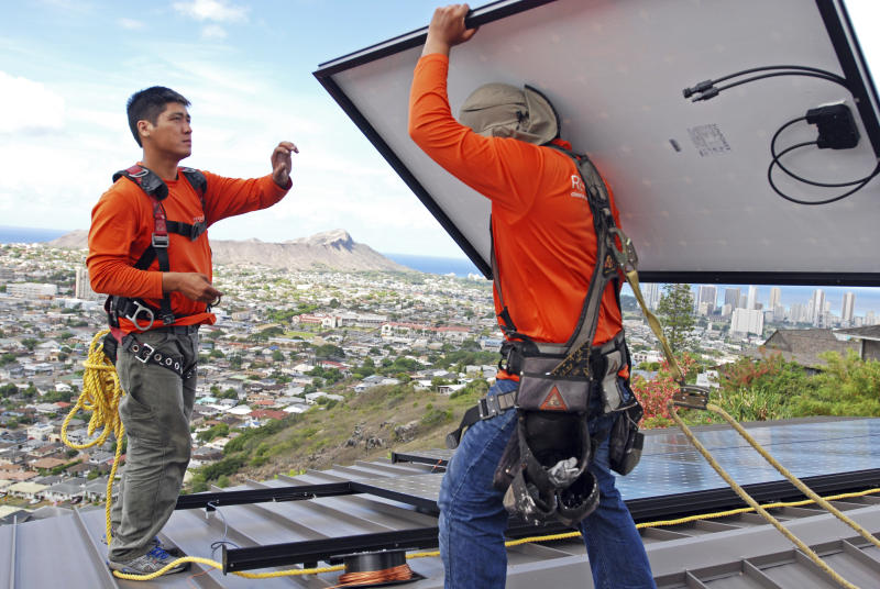 FILE - In this July 8, 2016, file photo, Dane Hew Len, left, lead installer for RevoluSun, and installer Radford Takashima place solar panels on a roof in Honolulu. If you have the cash, most experts agree buying a solar system outright is a better investment than leasing or taking out a loan. Customers should check electric bills to estimate monthly energy use when deciding what size system to buy, and calculate federal or state incentives. (AP Photo/Cathy Bussewitz, File)