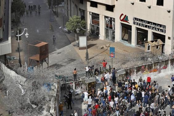 Anti-government protesters try to remove a concrete wall installed by security forces in Beirut, Lebanon (AP)