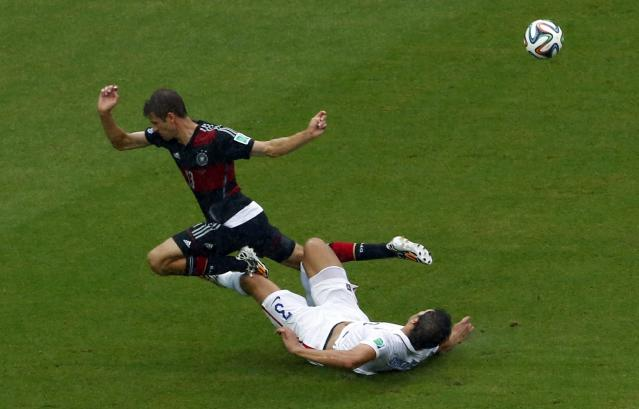 Germany's Thomas Mueller falls over Omar Gonzalez of the U.S. during their 2014 World Cup Group G soccer match at the Pernambuco arena in Recife June 26, 2014. REUTERS/Ruben Sprich (BRAZIL - Tags: SOCCER SPORT WORLD CUP)