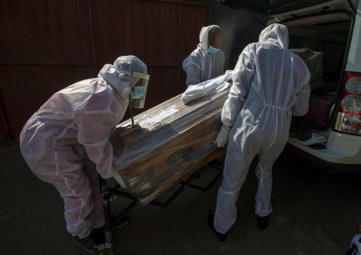 FILE - In this July 21 2020, file photo, funeral home workers in protective suits carry the coffin of a woman who died from COVID-19 into a hearse in Katlehong, near Johannesburg, South Africa. Africa's confirmed coronavirus cases have surpassed 1 million, but global health experts tell The Associated Press the true toll is several times higher. (AP Photo/Themba Hadebe, File)