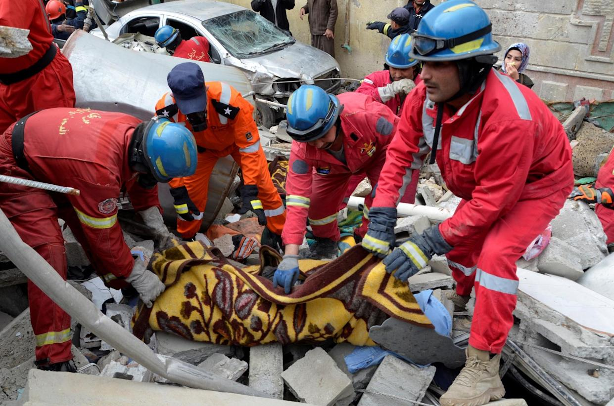 Firefighters carry the body of a victim of the airstrikein Mosul. (Reuters)