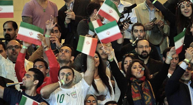 """Iranian fans cheer as Iranin wrestlers compete in an exhibition wrestling match at Grand Central Terminal, Wednesday, May 15, 2013, in New York. """"The Rumble on the Rails"""" exhibition, featuring teams from the United States, Iran and Russia, raises money for charity but is also aimed at drawing attention to the sport's attempt to stay in the Olympics. (AP Photo/Bebeto Matthews)"""