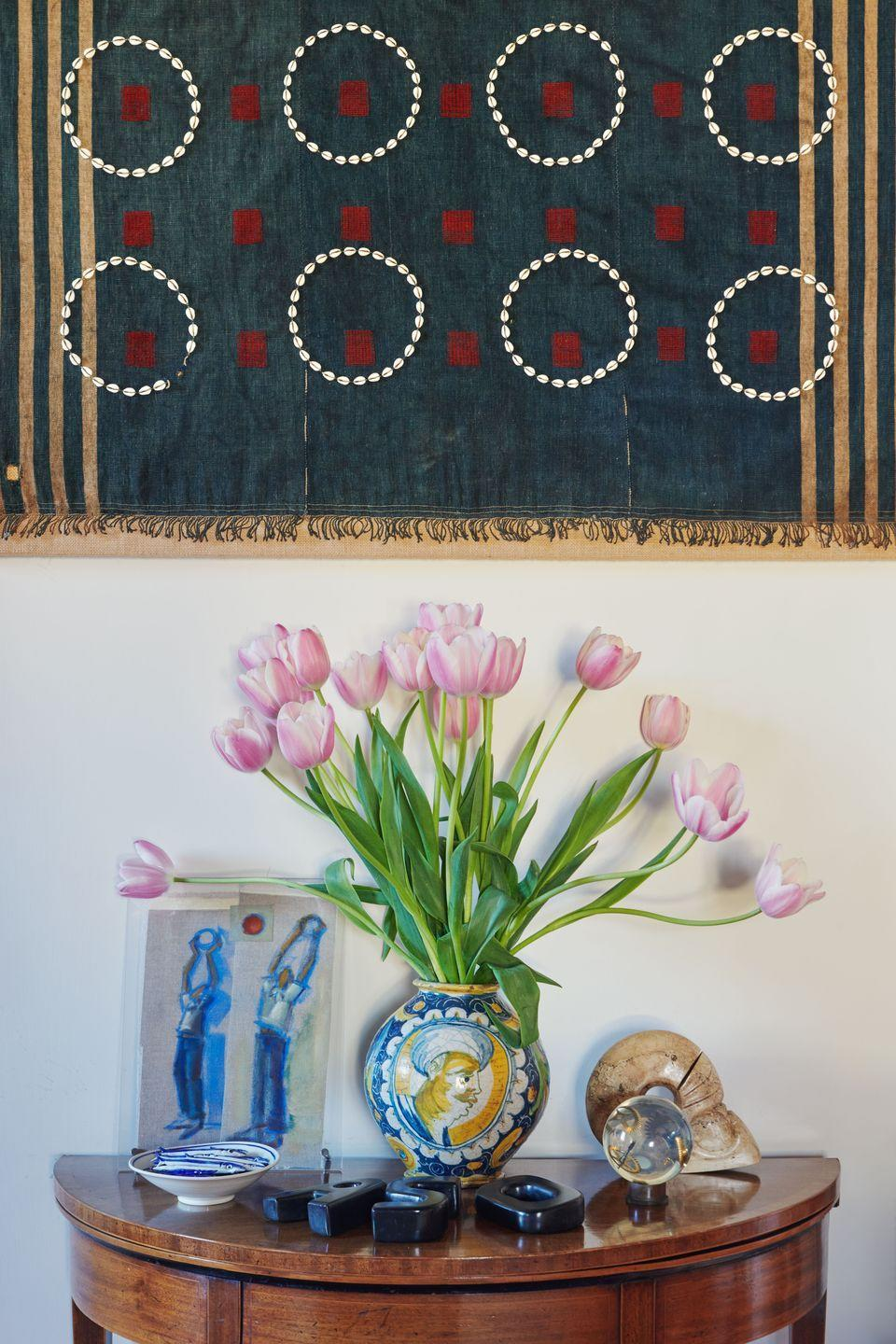 """<p>""""This blue textile is embroidered with circles of cowrie white shells and is a Chang Naga Warrior ceremonial textile body cloth. The vase is probably Sicilian and comes from my side of the family.""""</p>"""