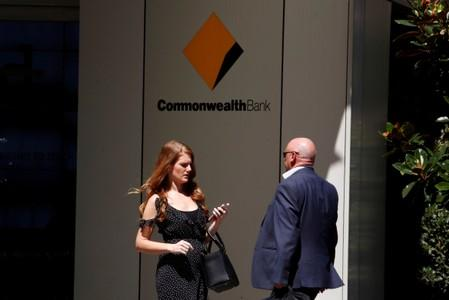 FILE PHOTO: Office workers walk in front of the Commonwealth Bank of Australia building in central Sydney