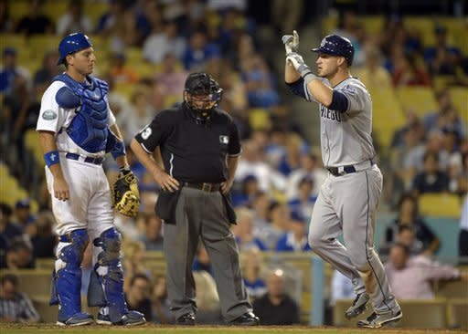 San Diego Padres' Yasmani Grandal, right, celebrates after hitting a two-run home run as Los Angeles Dodgers catcher A.J. Ellis, left, and home plate umpire Derryl Cousins look on during the eighth inning of their baseball game, Tuesday, Sept. 4, 2012, in Los Angeles. (AP Photo/Mark J. Terrill)