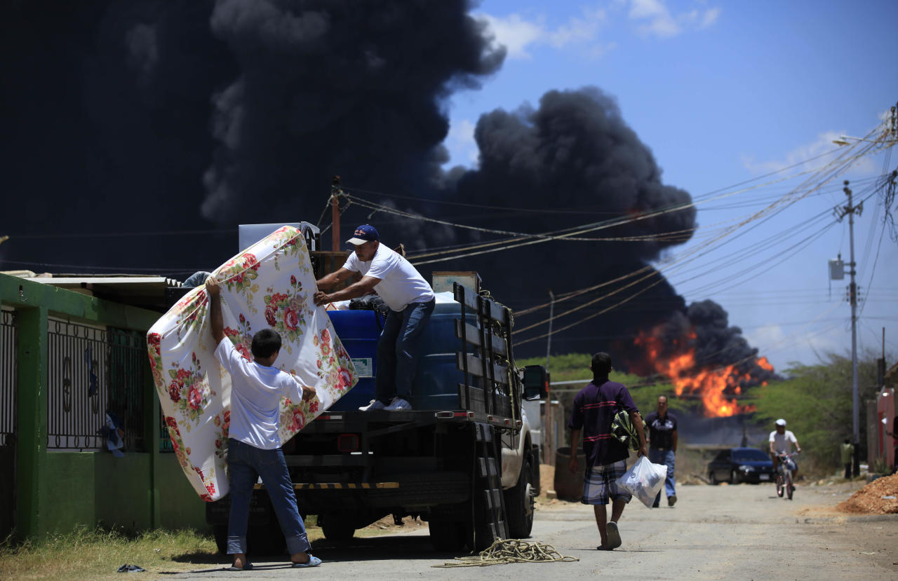 Family members load belongings onto a truck as they evacuate their damaged home after an explosion in the Amuay refinery near Punto Fijo, Venezuela, Sunday, Aug. 26, 2012. Venezuelans who live next to the country's biggest oil refinery said they smelled a strong odor of sulfur hours before a gas leak ignited in an explosion on Saturday that killed at least 39 people and injured more than 80. (AP Photo/Ariana Cubillos)