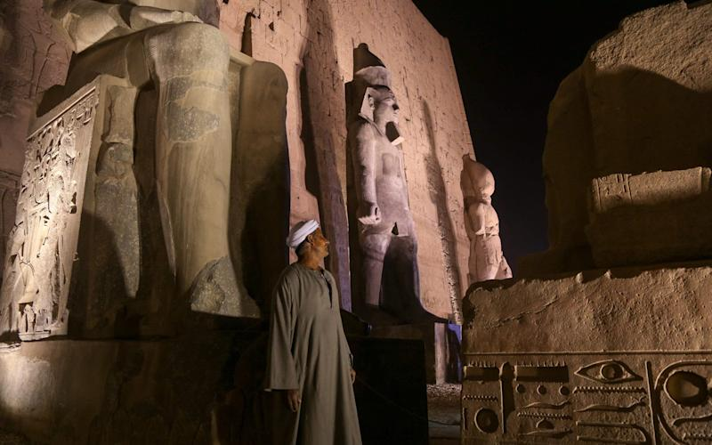 A man stands near a newly restored colossus statue of king Ramses II (C) at the Luxor Temple in Luxor, Egypt - Credit: Xinhua/Ahmed Gomaa