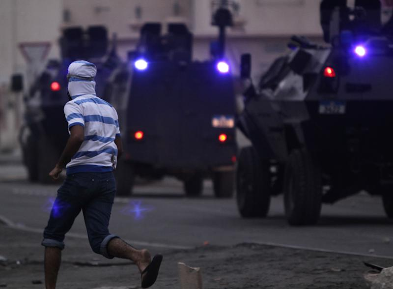 A Bahrain anti-government protester runs toward armored vehicles Friday, March 30, 2012, in Sitra, Bahrain, where widespread demonstrations remembering those who've died in the past year's unrest were broken up by police firing tear gas and clashes erupted. Amnesty International on Friday urged Bahrain to free a leading human rights activist who is on a hunger strike and reminded the Gulf kingdom's rulers to fulfill promises to release all those jailed for speaking out during the country's uprising. (AP Photo/Hasan Jamali)