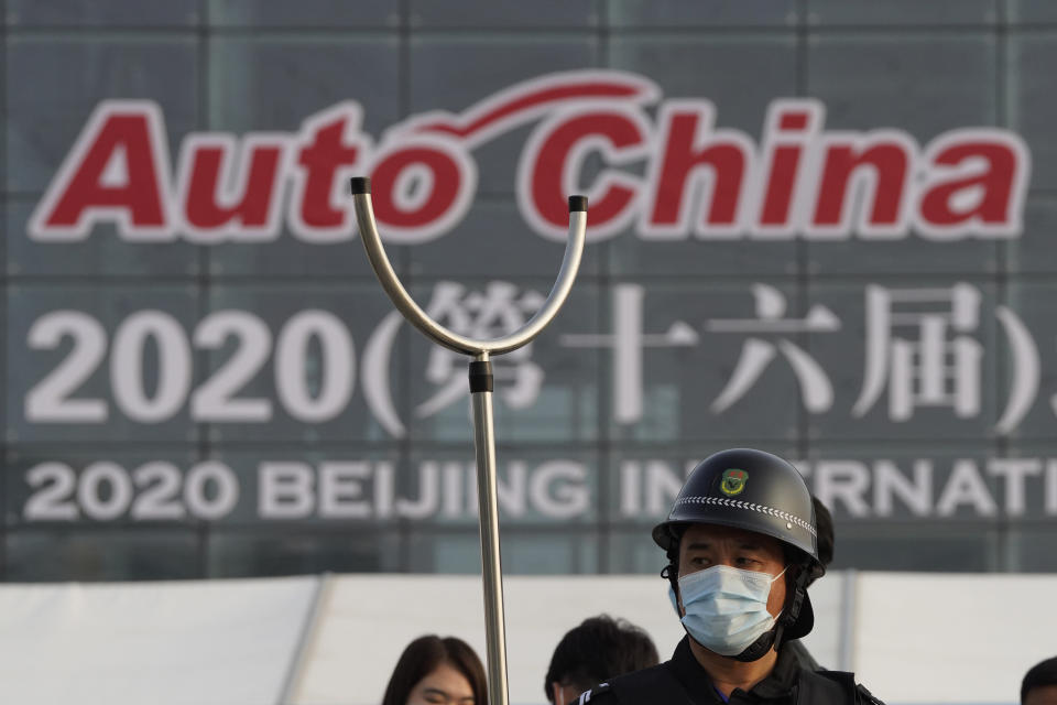 A security guard wearing mask and armed with a restrainer stands guard at the entrance to the Auto China 2020 show in Beijing, China on Saturday, Sept. 26, 2020. The auto show, the first major in-person sales event for any industry since the coronavirus pandemic began, opens Saturday in a sign the ruling Communist Party is confident China has contained the disease. Still, automakers face intensive anti-virus controls including quarantines for visitors from abroad and curbs on crowd sizes at an event that usually is packed shoulder-to-shoulder with spectators. (AP Photo/Ng Han Guan)