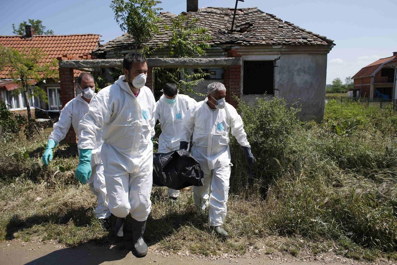 Serbian forensic specialists remove a body in front of a flooded house in Obrenovac, southwest of Belgrade, May 20, 2014. Soldiers and energy workers stacked thousands of sandbags overnight to protect Serbia's biggest power plant from flood waters expected to keep rising after the heaviest rains in the Balkans in more than a century killed dozens of people.REUTERS/Marko Djurica (SERBIA - Tags: DISASTER ENVIRONMENT)