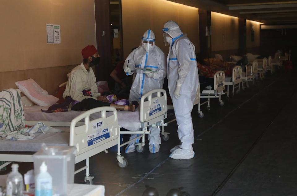 Indian doctors wearing Personal Protective Equipment (PPE)  examine patients inside a COVID 19 care centre and isolation ward facility near a Hospital in New Delhi, 13 April 2021.