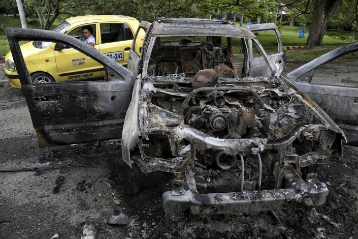 A taxi drives past the charred remains of a car that was burned during clashes between Indigenous people from Cauca state who arrived to support the national strike, with local residents who do not support the blocking of roads in Cali, Colombia, Monday, May 10, 2021. Colombians have protested across the country against a government they feel has long ignored their needs, allowed corruption to run rampant and is so out of touch that it proposed tax increases during the coronavirus pandemic. (AP Photo/Andres Gonzalez)