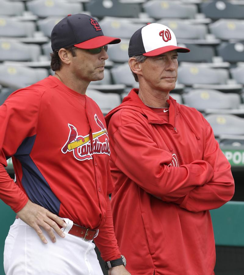 St. Louis Cardinals manager Mike Matheny, left, talks to Washington Nationals bullpen coach Jim Lett  before an exhibition spring training baseball game, Saturday, March 2, 2013, in Jupiter, Fla. (AP Photo/Julio Cortez)