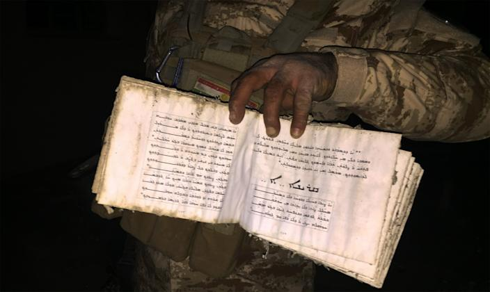 Christian peshmerga fighter holds open a Bible in the desecrated church of Batnay, Iraq. (Photo: Ash Gallagher for Yahoo News)