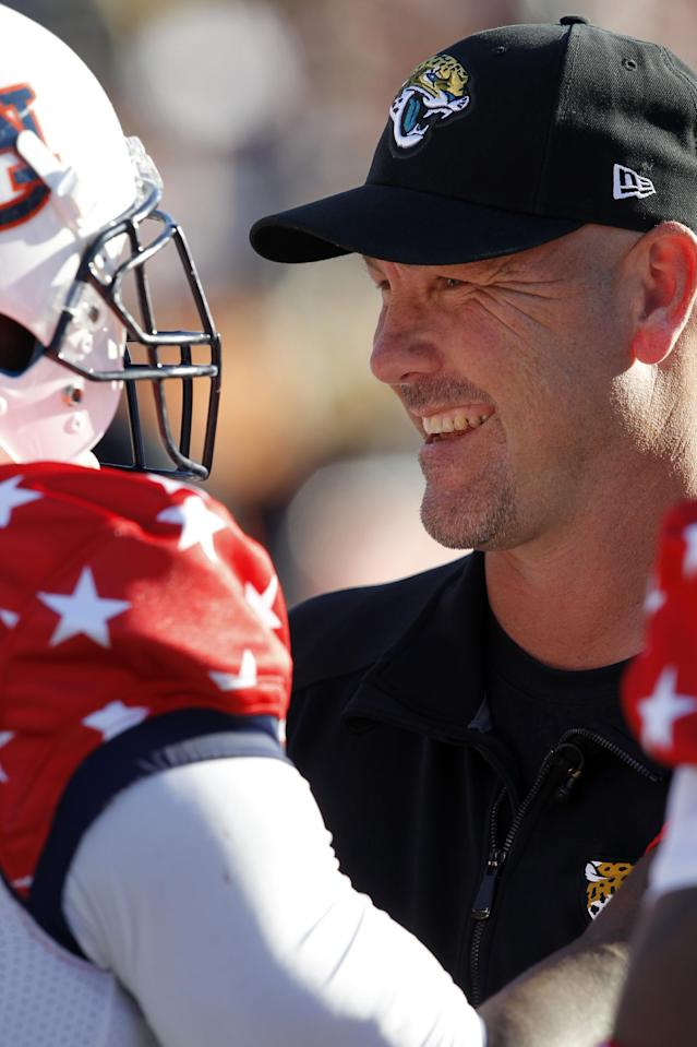 South coach Gus Bradley, of the Jacksonville Jaguars, talks with Dee Ford, of Auburn, on the sidelines during the first half of the Senior Bowl NCAA college football game on Saturday, Jan. 25, 2014, in Mobile, Ala. (AP Photo/Butch Dill)