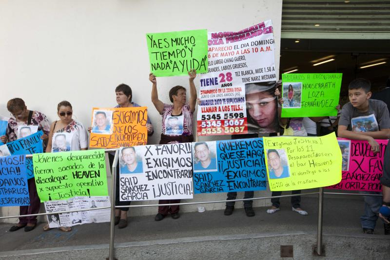Friends and family hold signs asking for justice for the persons they believe were abducted in broad daylight, outside the office of chief prosecutor Rodolfo Rios, in Mexico City, Tuesday, June 4, 2013. Another young woman has been added to the list of young people apparently abducted as a group on May 26, 2013 from an after-hours bar in a normally calm district of Mexico City, raising the number of missing to 12. Rios also announced that two of the bar's waiters and a woman he did not identify had been detained in the case. (AP Photo/Ivan Pierre Aguirre)