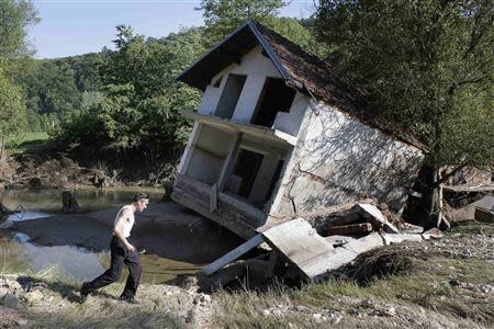 A man walks past a house tilted by floods in the town of Valjevo, southwest from Belgrade