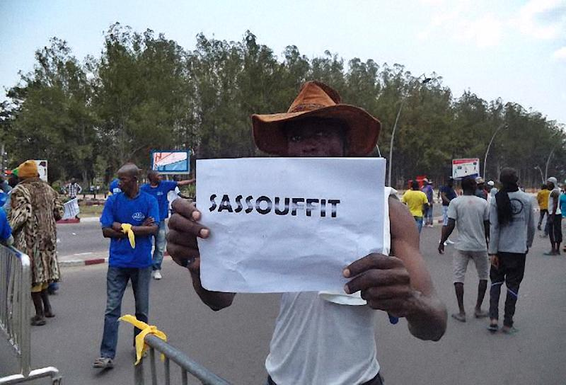 """A man holds a placard with a play on words referring to the Congolese president and reading """"Sassou enough"""" during an opposition demonstration in Brazzaville on September 27, 2015 (AFP Photo/Laudes Martial Mbon)"""