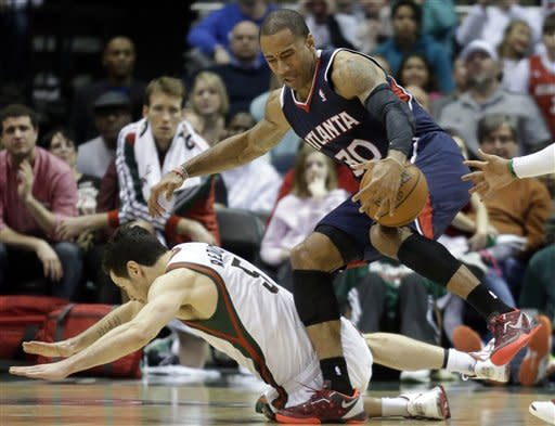 Atlanta Hawks' Dahntay Jones (30) and Milwaukee Bucks' J.J. Redick battle for a loose ball during the second half of an NBA basketball game on Sunday, March 24, 2013, in Milwaukee. The Hawks won 104-99. (AP Photo/Morry Gash)