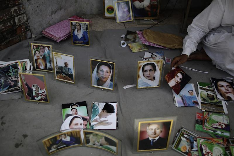 Pakistani vendor, Mohammed Ashraf, 65, displays photographs of Pakistan's slain leader Benazir Bhutto for sale at the site where she was killed, in Rawalpindi, Pakistan, Monday, April 8, 2013. Pakistan's top court on Monday ordered former military ruler Gen. Pervez Musharraf to respond to allegations that he committed treason while in power and barred him from leaving the country. The Taliban have threatened to kill him, and he faces a series of legal charges that he has denied, including some related to the 2007 assassination of former Prime Minister Benazir Bhutto. (AP Photo/Muhammed Muheisen)