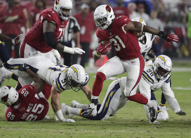 FILE - In this Saturday, Aug. 11, 2018, file photo, Arizona Cardinals running back David Johnson (31) breaks free against the Los Angeles Chargers during the first half of a preseason NFL football game, in Glendale, Ariz. Arizona has two of the NFC West's top players in cornerback Patrick Peterson and running back David Johnson, who is coming back from a wrist injury. (AP Photo/Rick Scuteri, File)