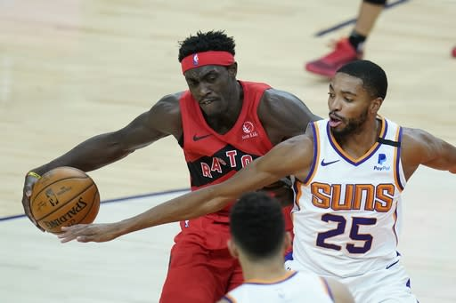 Toronto Raptors forward Pascal Siakam, left, tries to control the ball against Phoenix Suns forward Mikal Bridges (25) during the first half of an NBA basketball game Wednesday, Jan. 6, 2021, in Phoenix. (AP Photo/Ross D. Franklin)