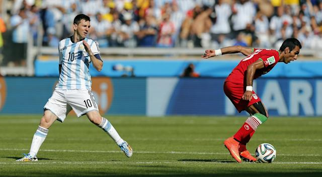 Argentina's Lionel Messi, left, watches as Iran's Mehrdad Pooladi takes the ball away from him during the group F World Cup soccer match between Argentina and Iran at the Mineirao Stadium in Belo Horizonte, Brazil, Saturday, June 21, 2014. (AP Photo/Victor R. Caivano)