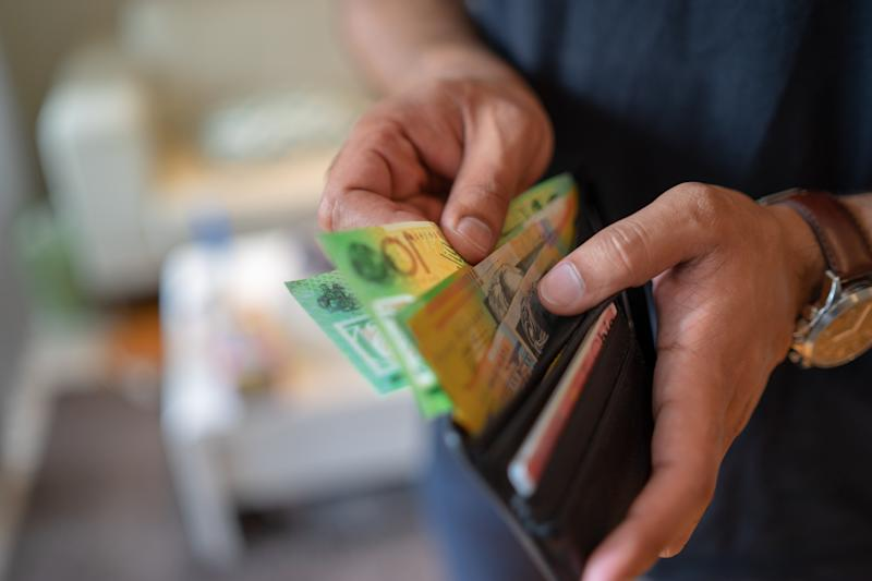 a male taking money out of the wallet.