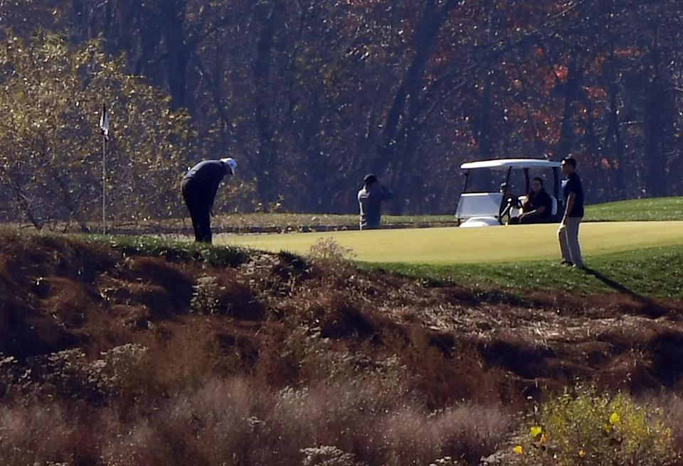 TOPSHOT - US President Donald Trump (L) golfs at Trump National Golf Club on November 7, 2020 in Sterling, Virginia. - Democrat Joe Biden has won the White House, US media said November 7, defeating Donald Trump and ending a presidency that convulsed American politics, shocked the world and left the United States more divided than at any time in decades. (Photo by Olivier DOULIERY / AFP) (Photo by OLIVIER DOULIERY/AFP via Getty Images)