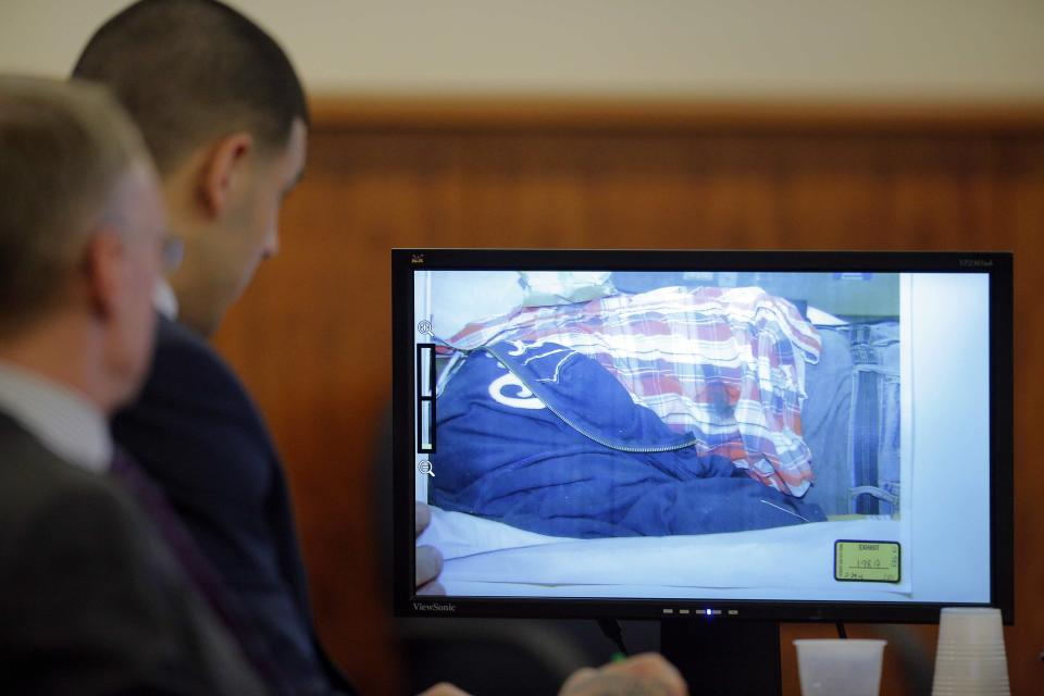 Former New England Patriots player, Aaron Hernandez (2nd L), looks at a photograph of the body of Odin Lloyd, displayed as evidence in Hernandez's murder trial at Bristol County Superior Court in Fall River, Massachusetts, February 24, 2015. Hernandez is accused of the murder of Odin Lloyd in June 2013. REUTERS/Brian Snyder (UNITED STATES - Tags: CRIME LAW SPORT FOOTBALL)