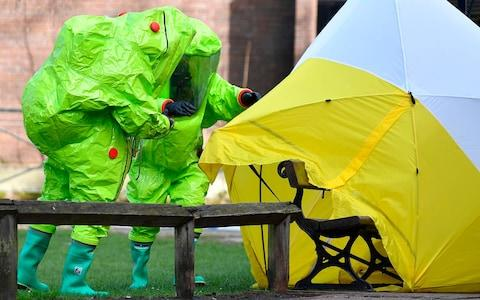 Members of the emergency services in green biohazard encapsulated suits afix a tent over the bench on which the Skripals were found - Credit: BEN STANSALL/AFP