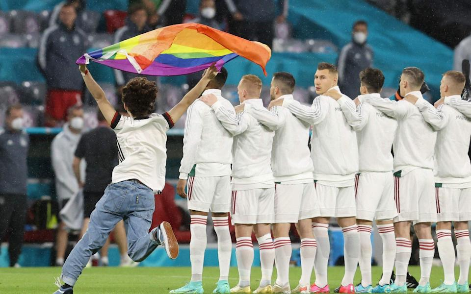 A person waving the rainbow flag runs on the pitch as the players line up for the national anthems the UEFA EURO 2020 Group F football match between Germany and Hungary at the Allianz Arena in Munich - GETTY IMAGES
