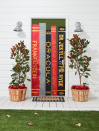 <p>Haunting book jackets make for a spine-chilling entrance. You can easily make these yourself using construction paper, some letter stencils, and a bit of gold craft paint.</p><p><strong>Make the Books: </strong>Cut long, thin rectangular pieces of differing colored kraft paper or construction paper (we used red, gray, and black). Draw titles of books on the paper. Outline letters with gold paint pens. Fill in outline with paint pen or gold acrylic paint. Attach to door with double- sided tape. </p>