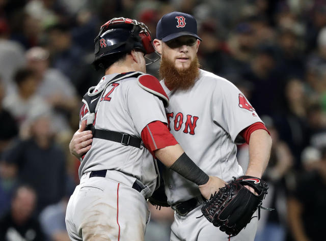 Boston Red Sox closing pitcher Craig Kimbrel, right, embraces catcher Christian Vazquez after the Red Sox defeated the Seattle Mariners 2-1 in a baseball game Thursday, June 14, 2018, in Seattle. (AP Photo/Elaine Thompson)